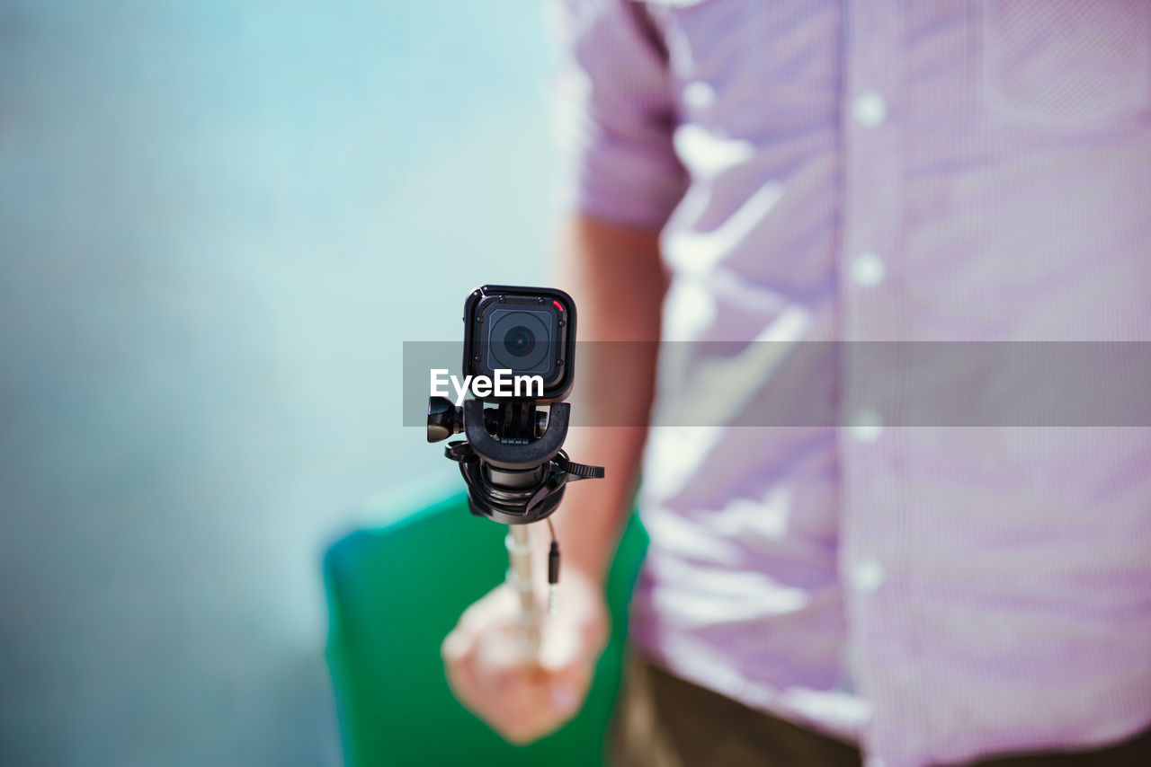Midsection of man holding wearable camera