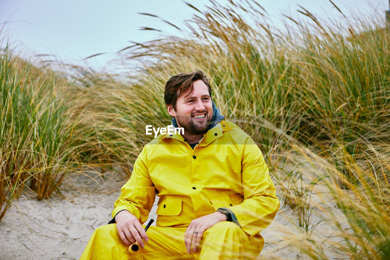 Smiling man sitting at beach against sky