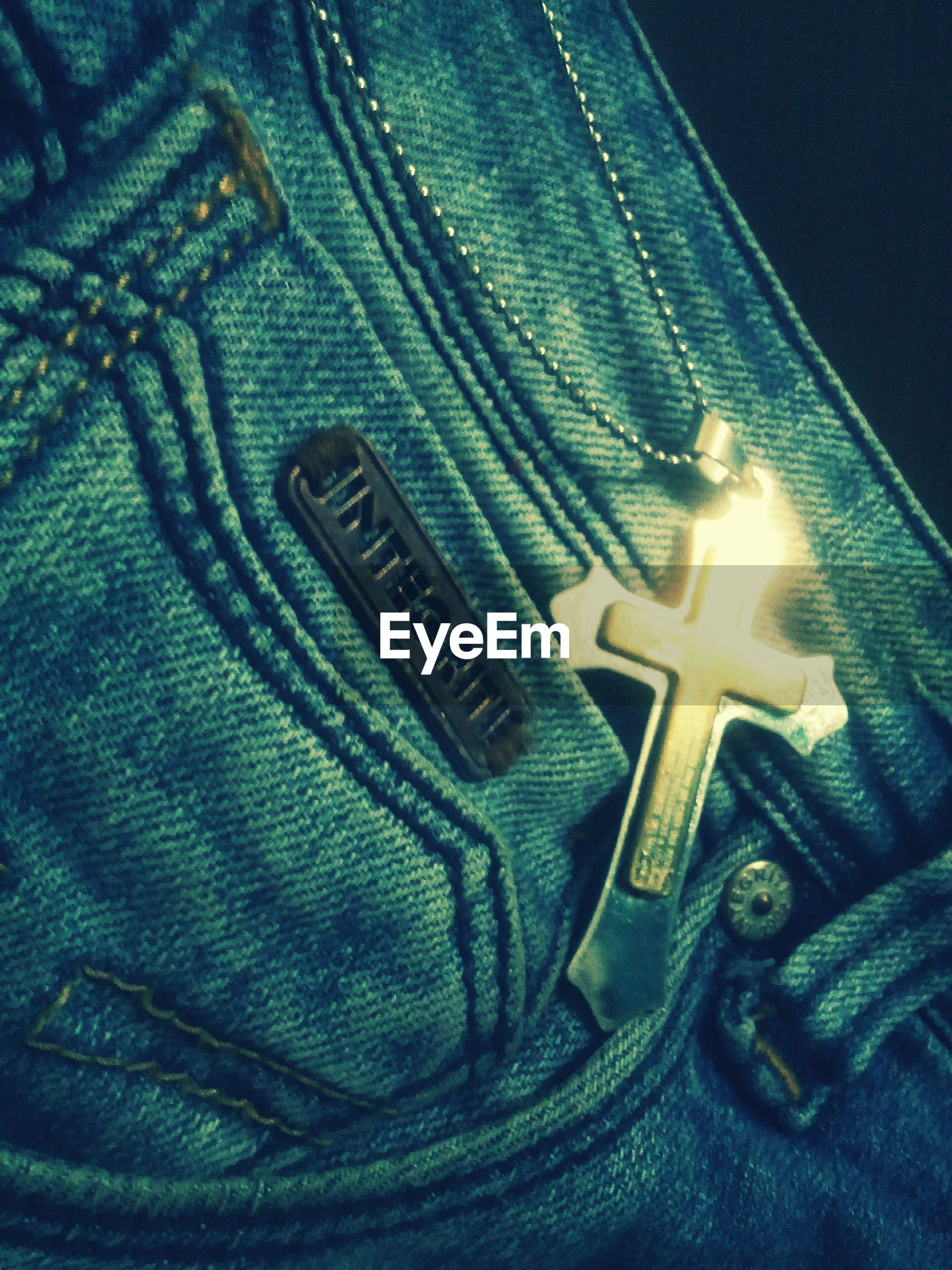 Close-up of cross on jeans