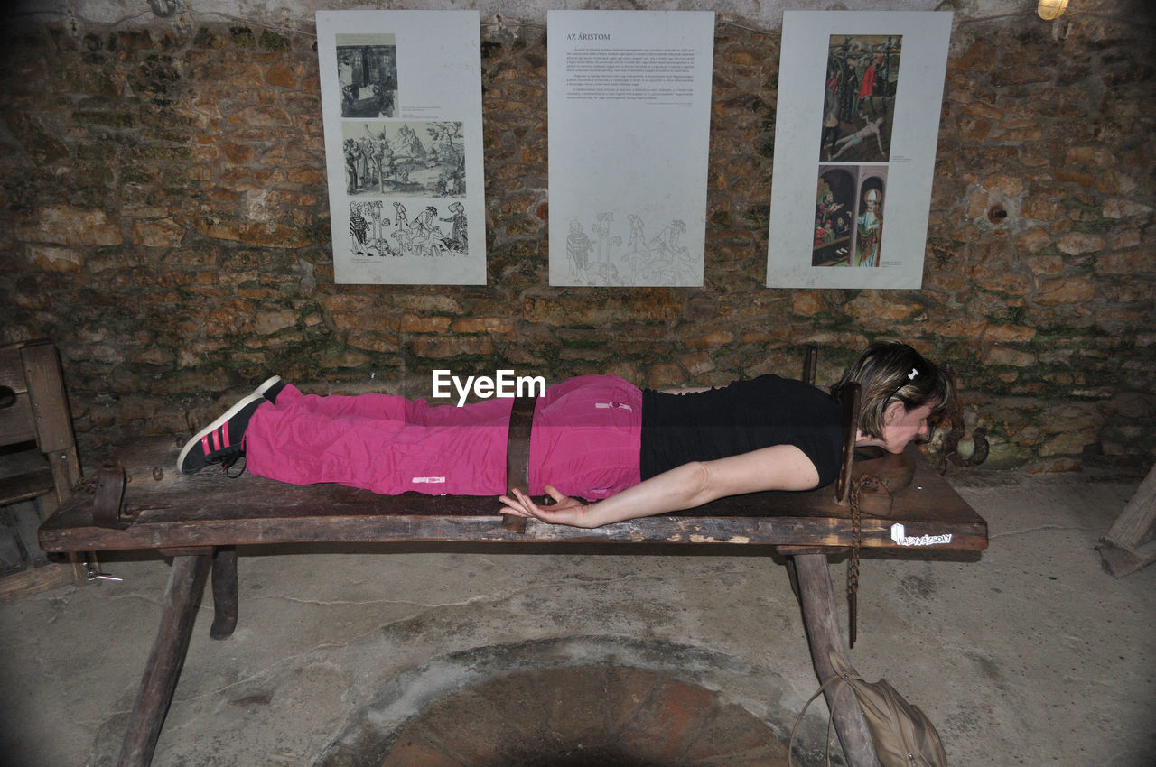 lying down, one person, young adult, relaxation, full length, casual clothing, young women, real people, wall - building feature, women, leisure activity, wall, indoors, lifestyles, lying on back, adult, sleeping, females, brick