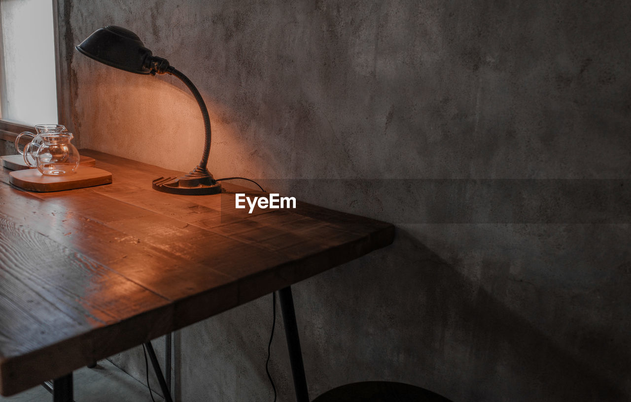 HIGH ANGLE VIEW OF EMPTY CHAIR BY TABLE AGAINST WALL