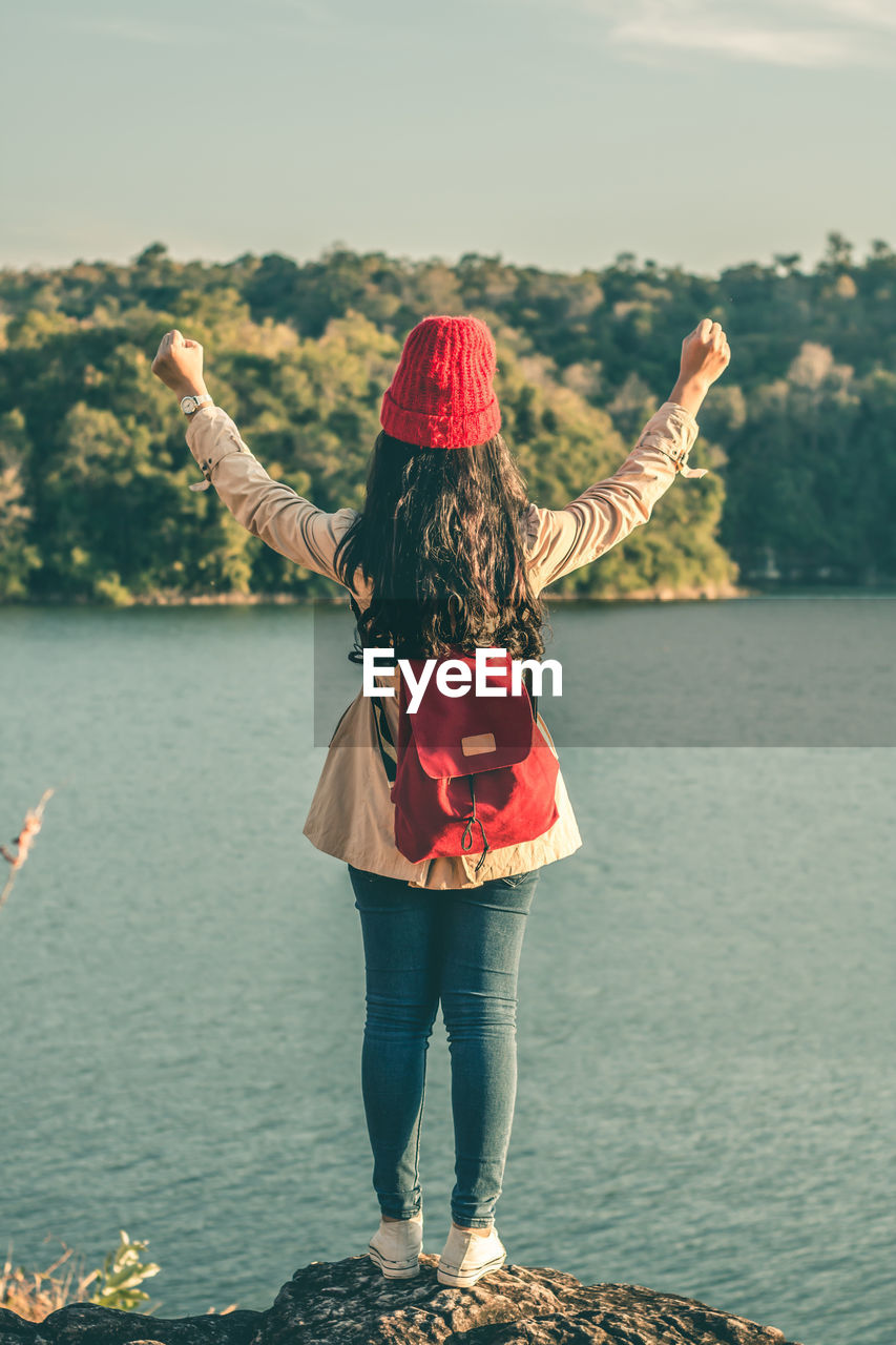 water, real people, rear view, women, lifestyles, nature, adult, standing, casual clothing, one person, leisure activity, human arm, hairstyle, hair, lake, full length, arms outstretched, day, clothing, limb, arms raised, outdoors, positive emotion