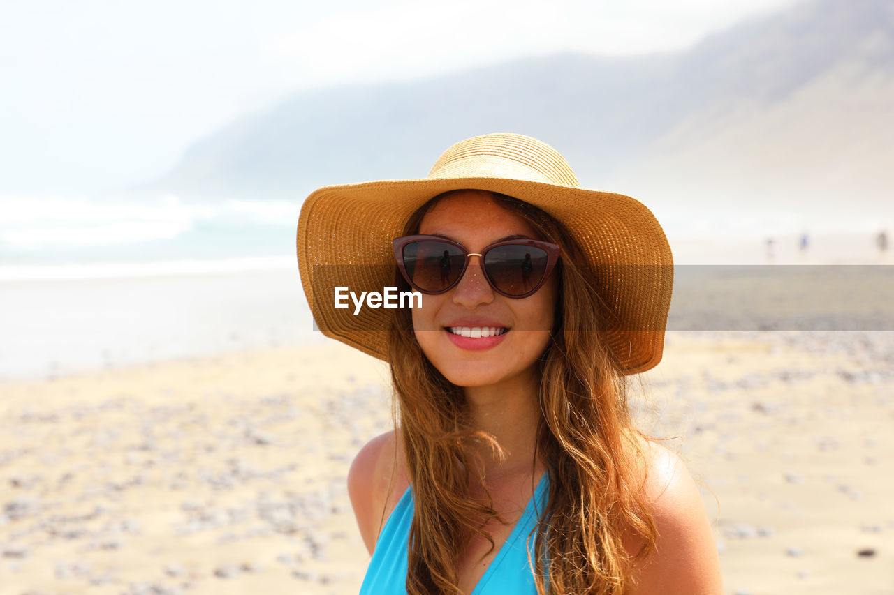 Portrait of smiling young woman wearing sunglasses at beach