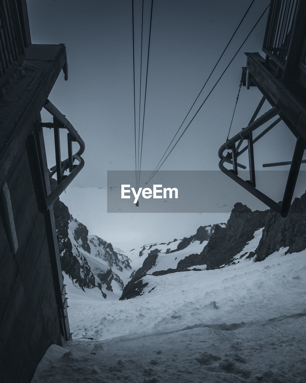 snow, winter, cold temperature, sky, scenics - nature, beauty in nature, mountain, transportation, nature, cable car, snowcapped mountain, ski lift, day, overhead cable car, tranquility, tranquil scene, cable, covering, mountain range, outdoors, no people, mountain peak, ski resort
