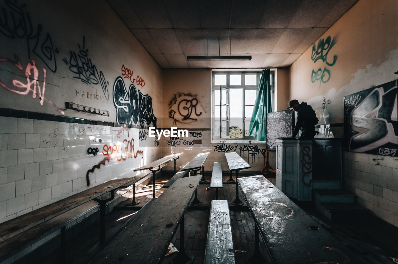 graffiti, indoors, architecture, wall - building feature, no people, abandoned, text, built structure, day, domestic room, art and craft, messy, obsolete, empty, building, creativity, absence, western script, run-down, deterioration, ceiling