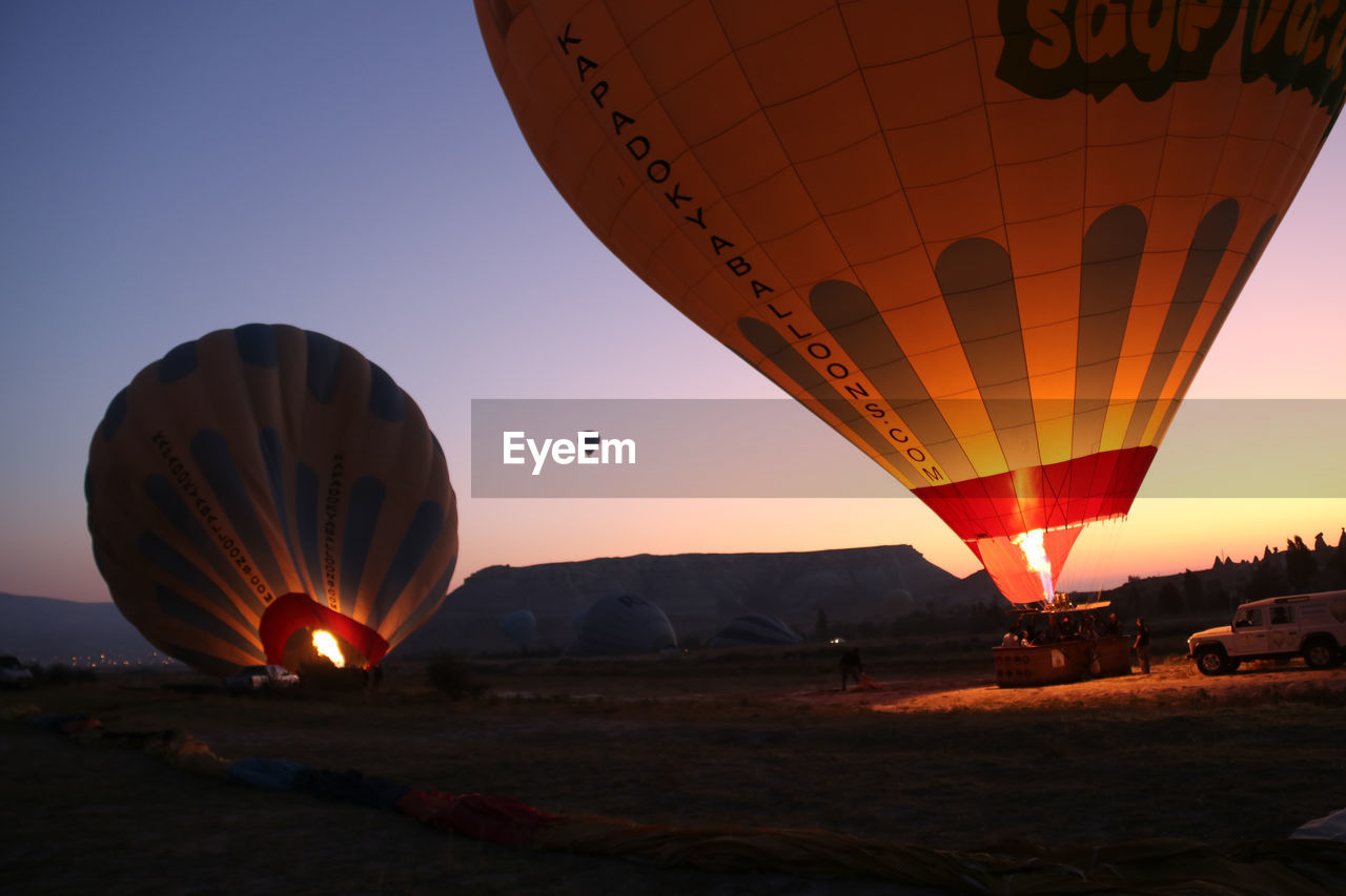 hot air balloon, air vehicle, balloon, nature, sky, transportation, sunset, ballooning festival, mode of transportation, land, adventure, flying, fire, burning, incidental people, travel, illuminated, outdoors, orange color, mid-air