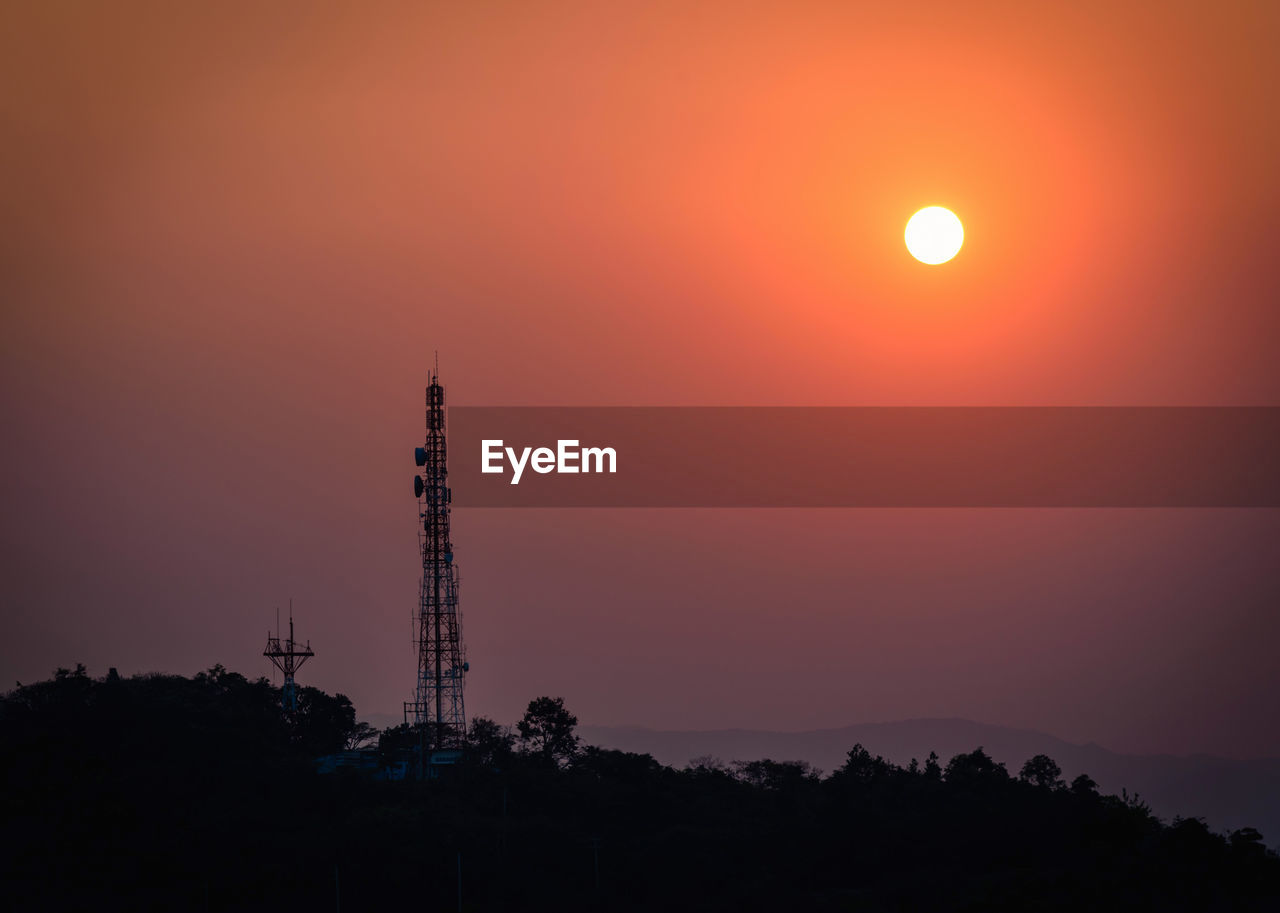 sky, sunset, orange color, sun, beauty in nature, silhouette, tower, built structure, scenics - nature, nature, architecture, plant, tree, technology, no people, outdoors, tall - high, building exterior, idyllic, connection