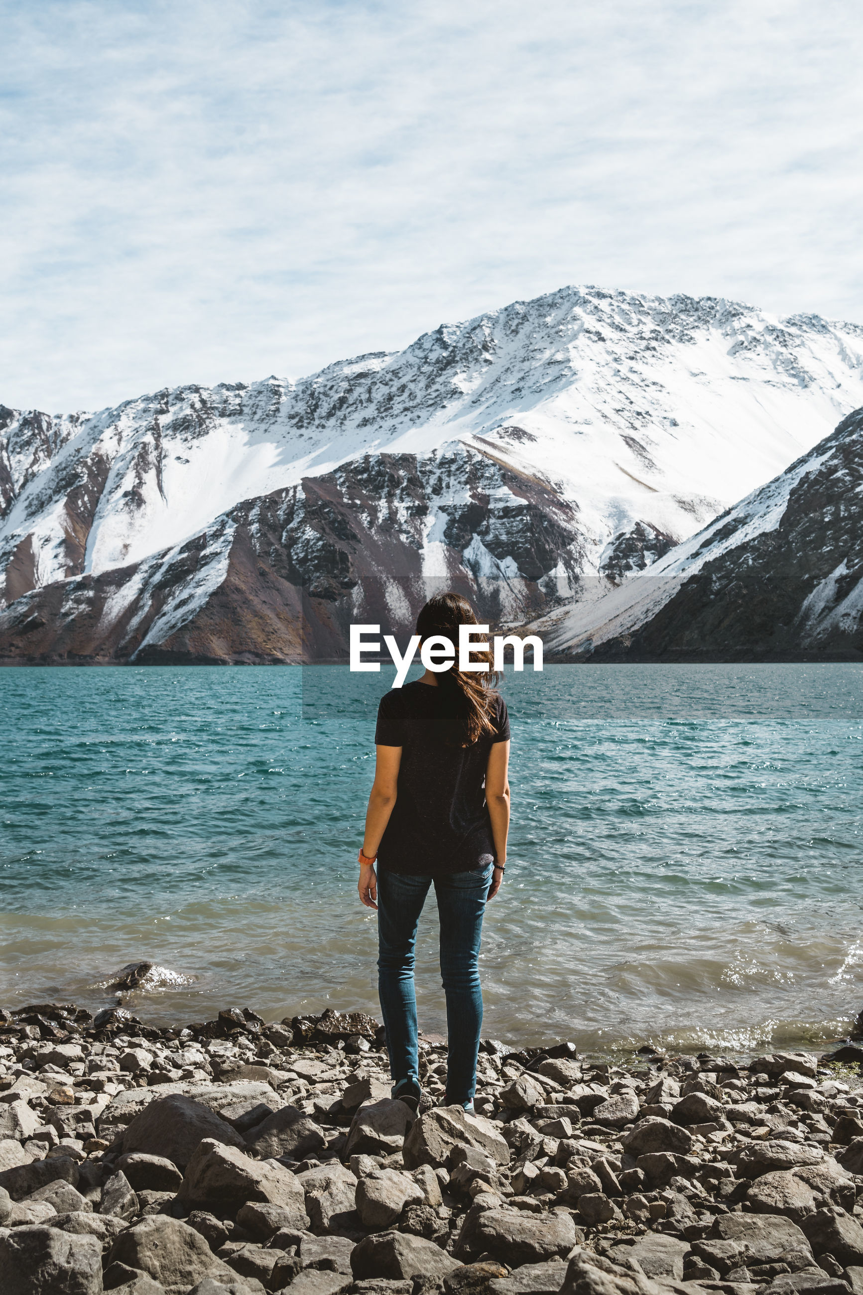 Rear view full length of woman standing at lakeshore against snowcapped mountain