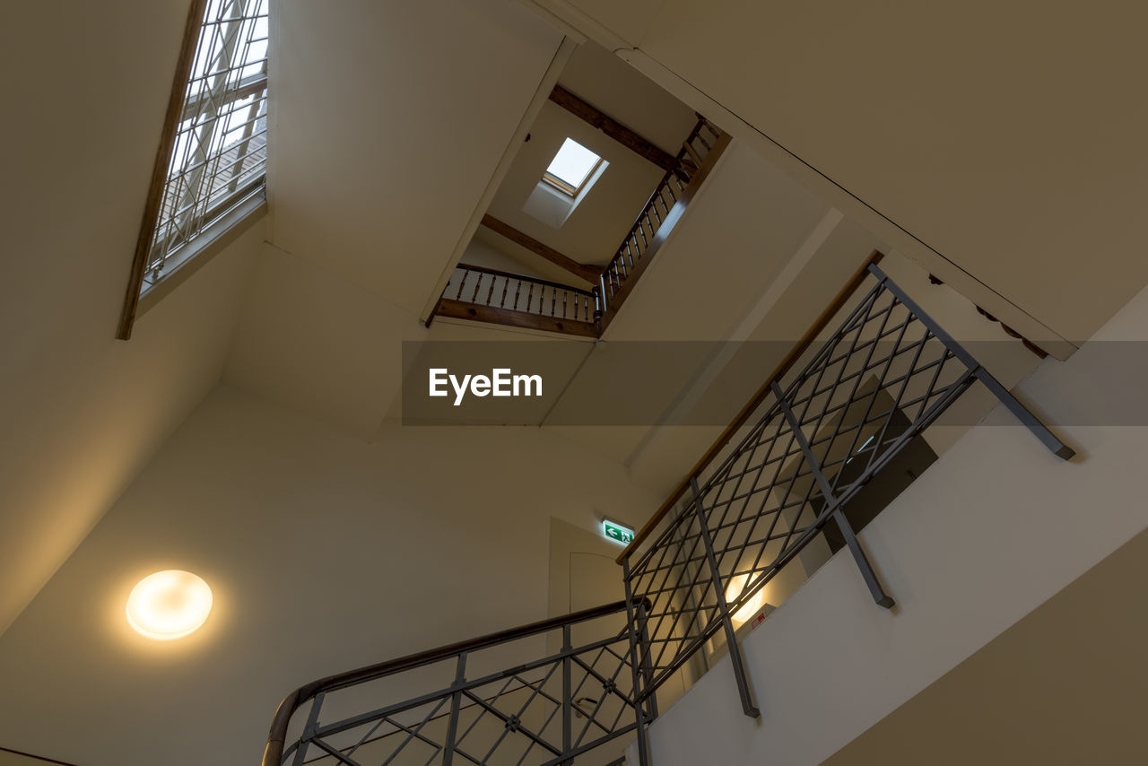 low angle view, architecture, indoors, lighting equipment, built structure, illuminated, ceiling, no people, window, railing, building, steps and staircases, staircase, wall - building feature, sunlight, home interior, skylight, metal, technology, electric lamp