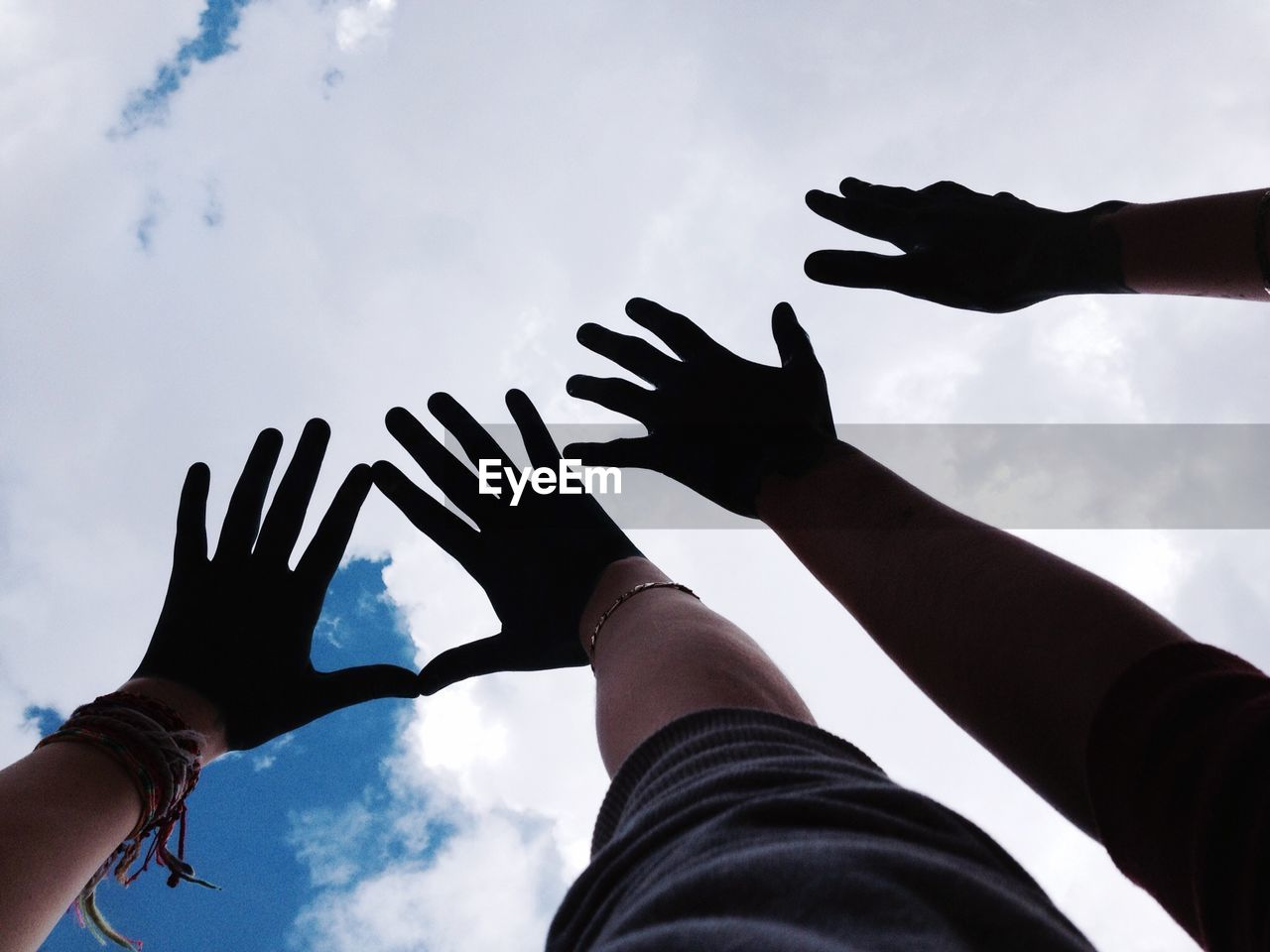 Cropped Image Of Hands Gesturing Against Sky