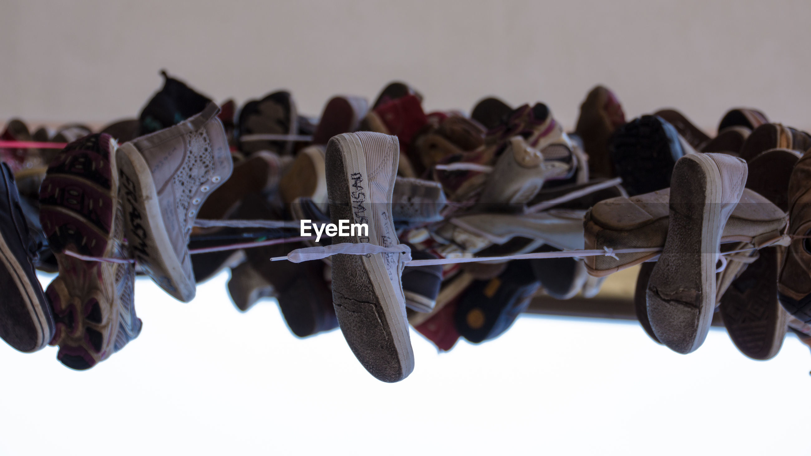 CLOSE-UP OF SHOES HANGING ON ROPE