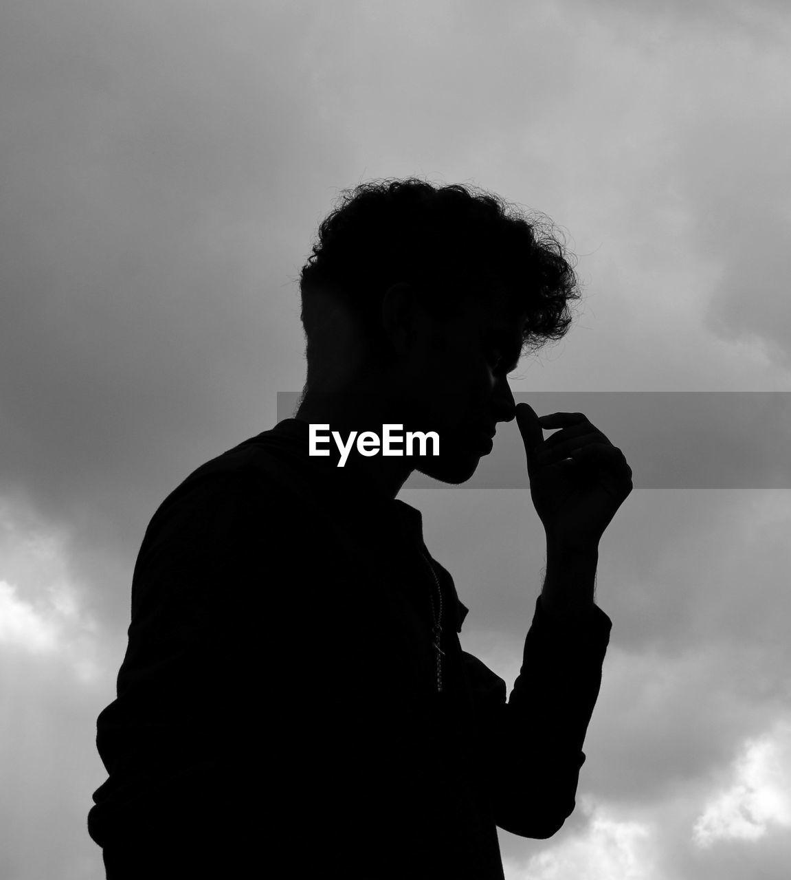 Silhouette man smoking cigarette against sky