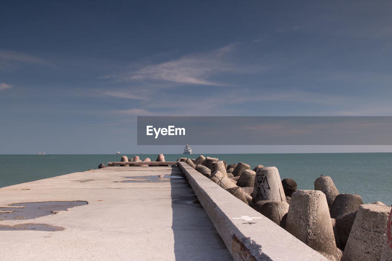 Pier By Groynes Against Sea And Sky