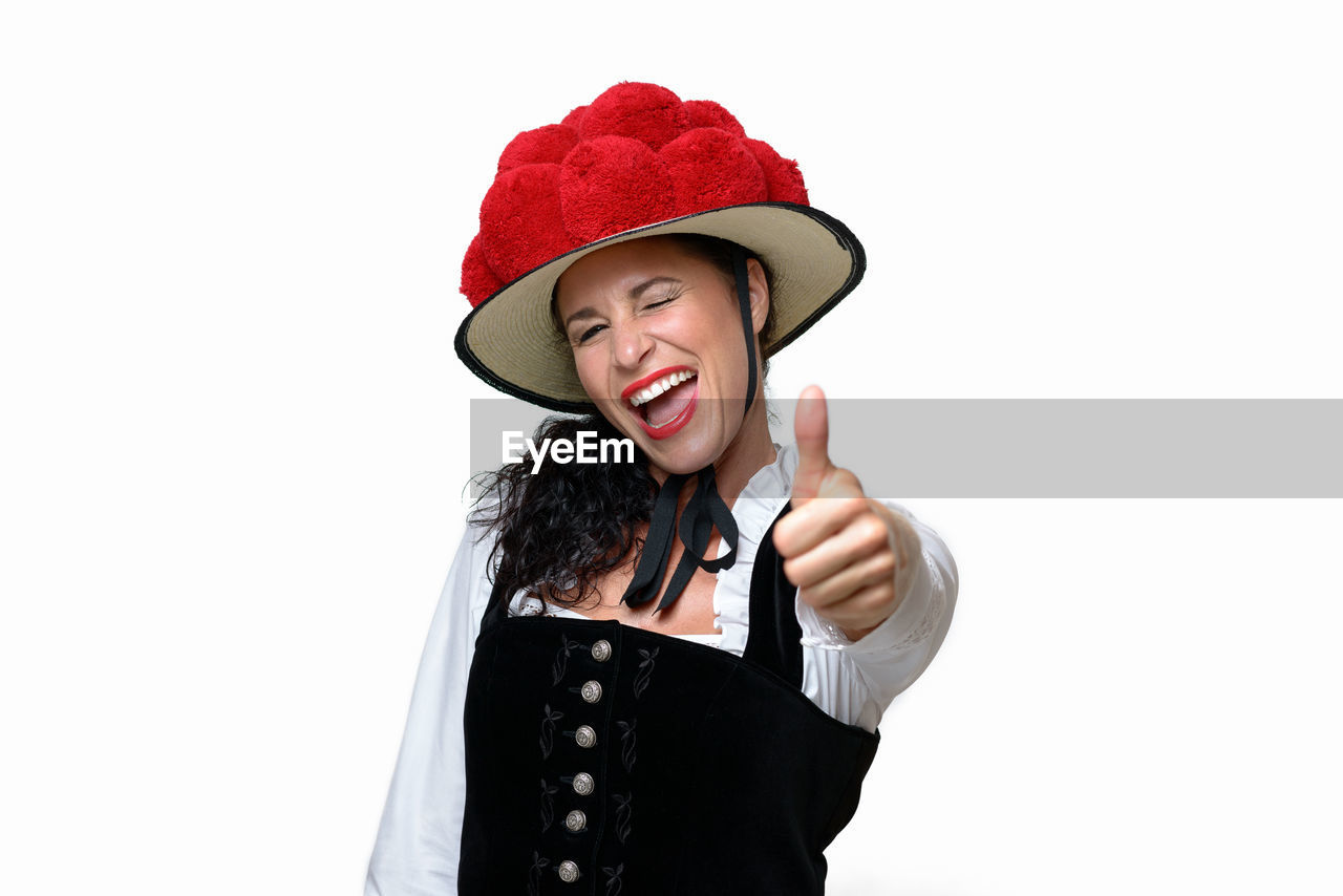 Portrait of cheerful waitress showing thumbs up sign while winking against white background