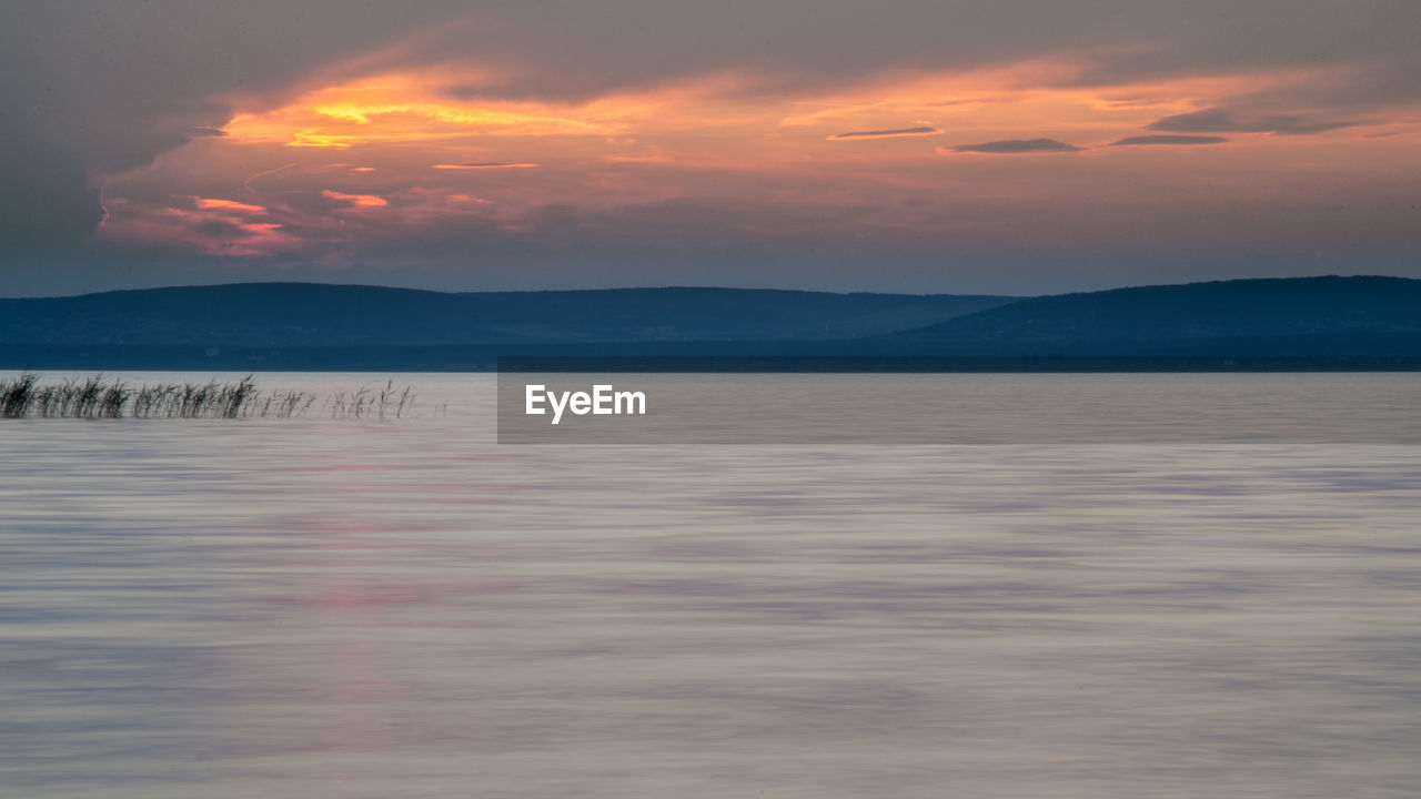sky, beauty in nature, scenics - nature, water, sunset, tranquil scene, cloud - sky, tranquility, waterfront, mountain, idyllic, orange color, no people, nature, sea, non-urban scene, mountain range, outdoors