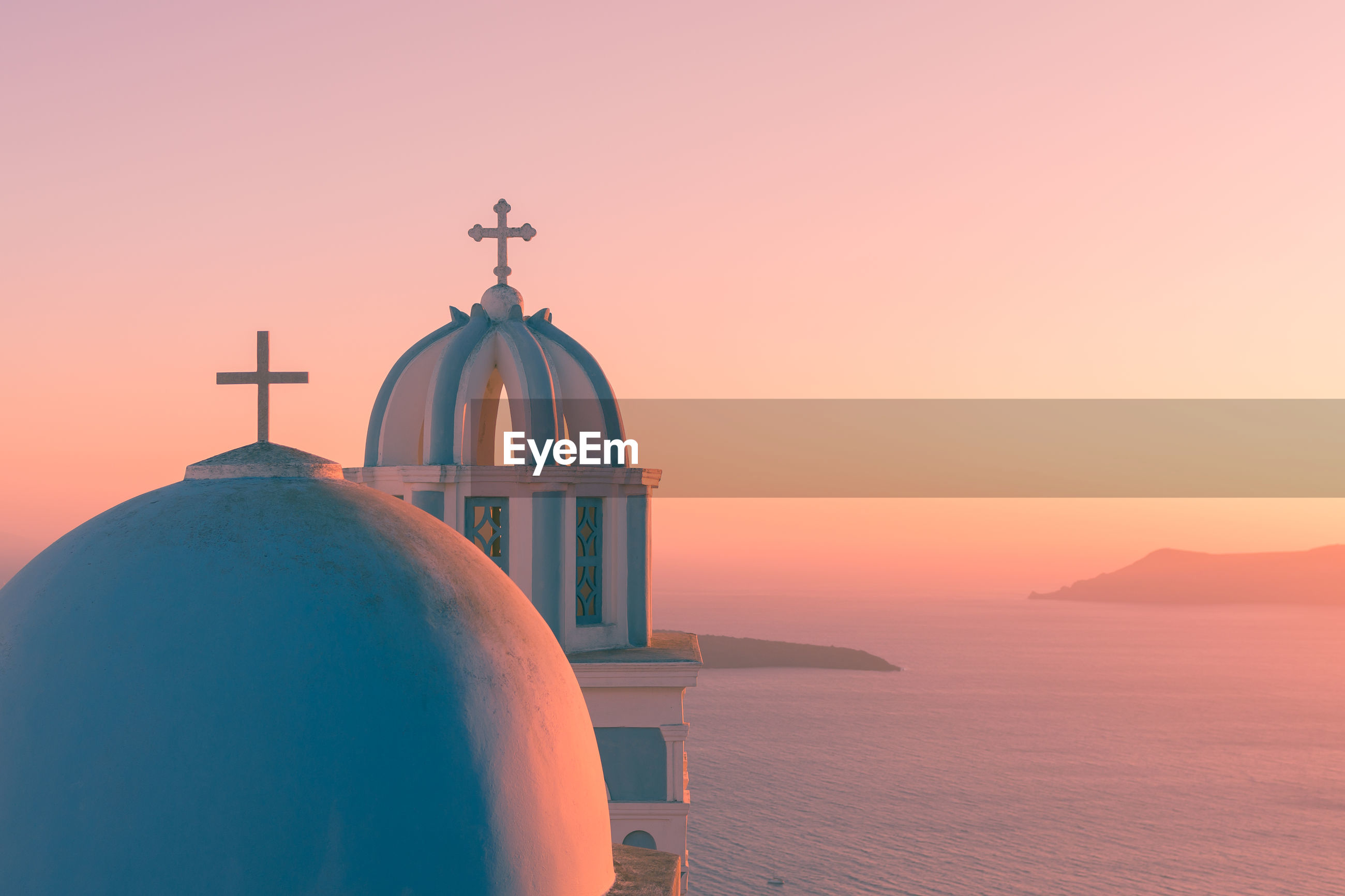 Church by sea against sky during sunset