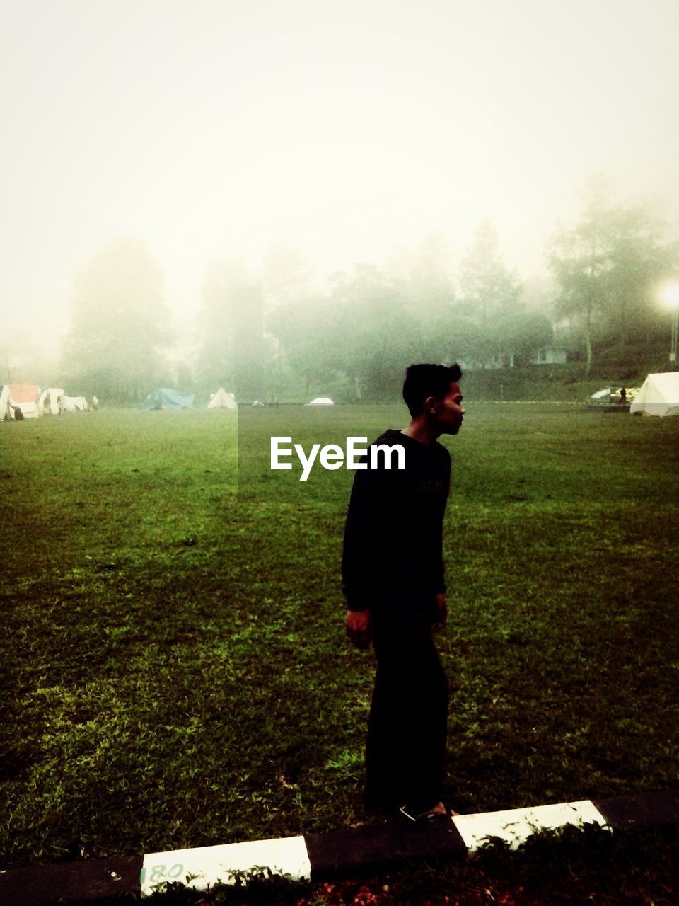 real people, field, one person, standing, nature, outdoors, day, grass, landscape, lifestyles, full length, tree, leisure activity, men, growth, fog, beauty in nature, sky, young adult, people