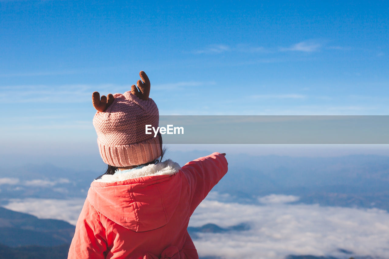 Rear view of girl standing against sky during winter