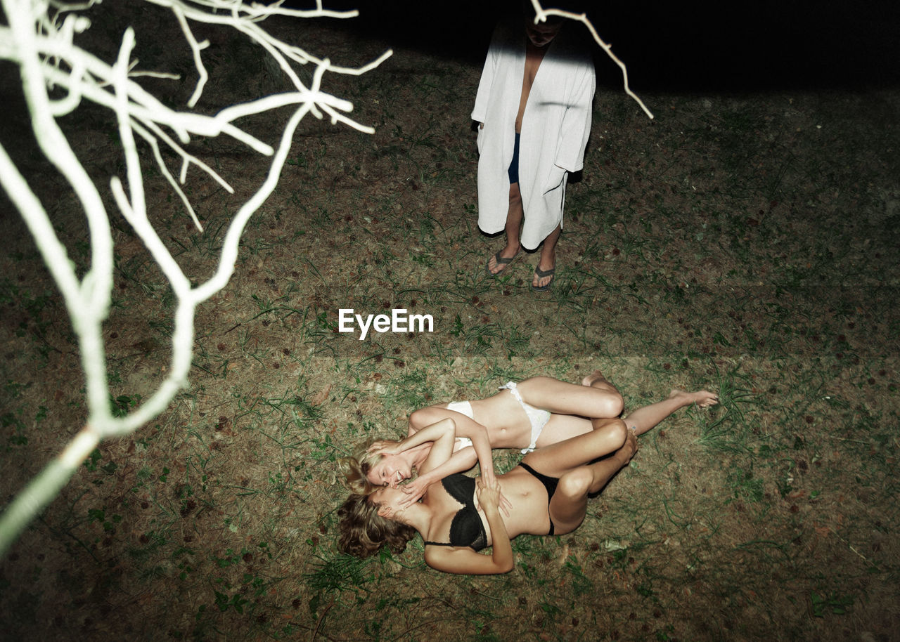 High Angle View Of Lesbians Romancing While Man Standing On Field At Night
