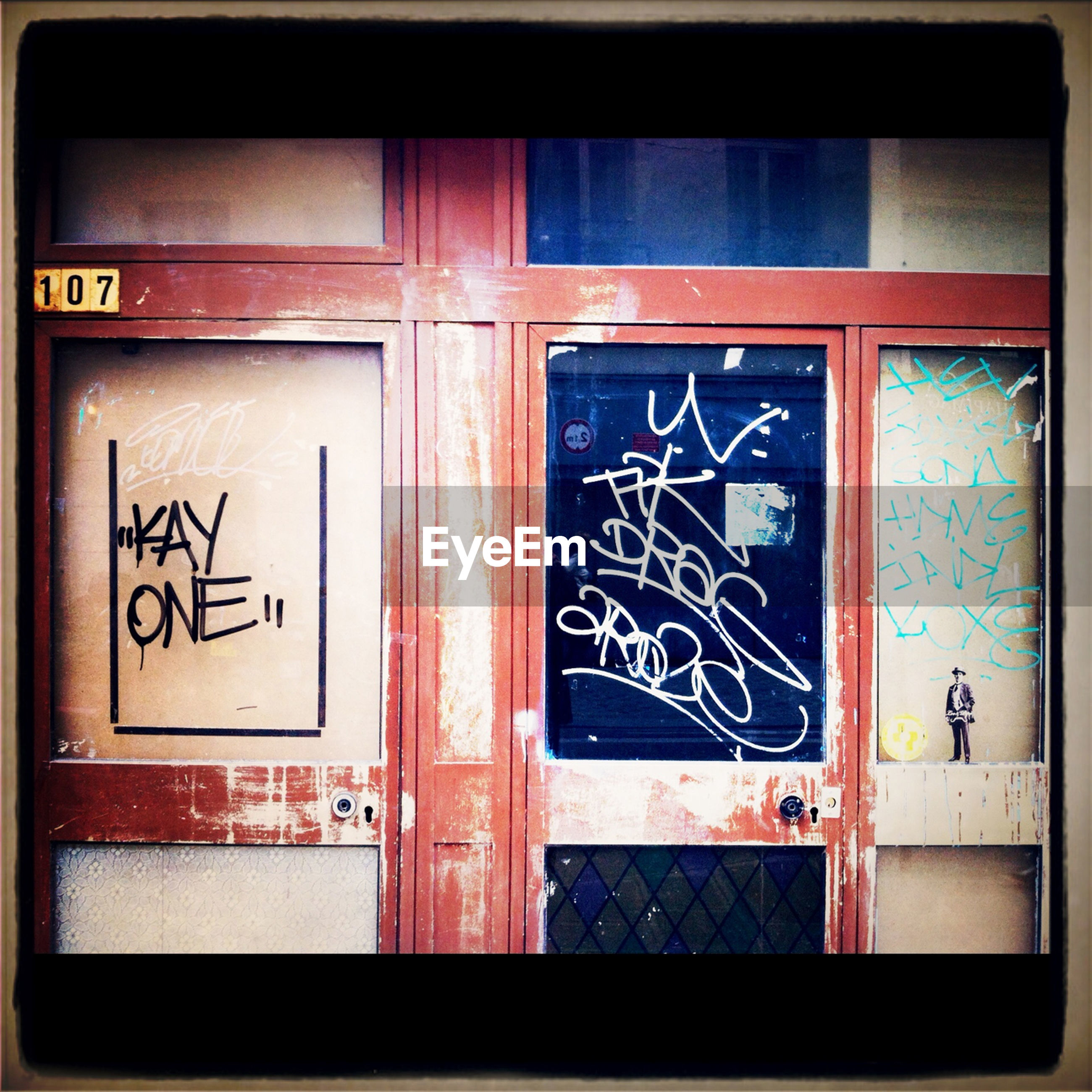 architecture, built structure, building exterior, door, closed, text, transfer print, graffiti, window, western script, wall - building feature, entrance, auto post production filter, communication, wall, safety, house, day, building, art
