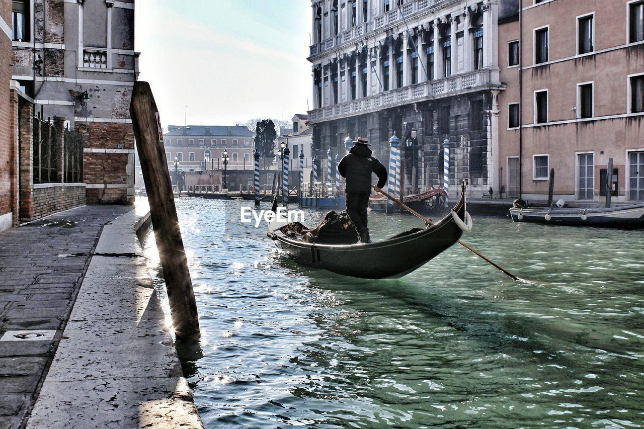 Men In Gondola On Canal In City Against Sky