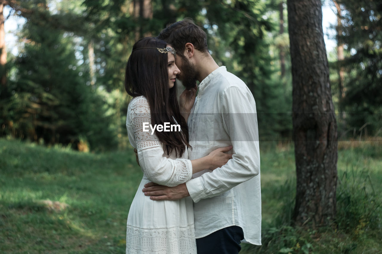 togetherness, love, two people, tree, young adult, couple - relationship, emotion, standing, positive emotion, focus on foreground, young men, bonding, real people, men, embracing, adult, women, young women, long hair, casual clothing, hairstyle, hair, outdoors