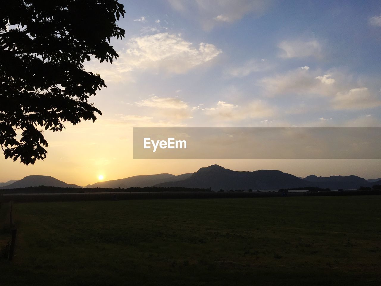 sky, scenics - nature, beauty in nature, tranquil scene, sunset, mountain, tranquility, environment, cloud - sky, plant, nature, landscape, land, no people, silhouette, field, mountain range, non-urban scene, grass, idyllic, outdoors