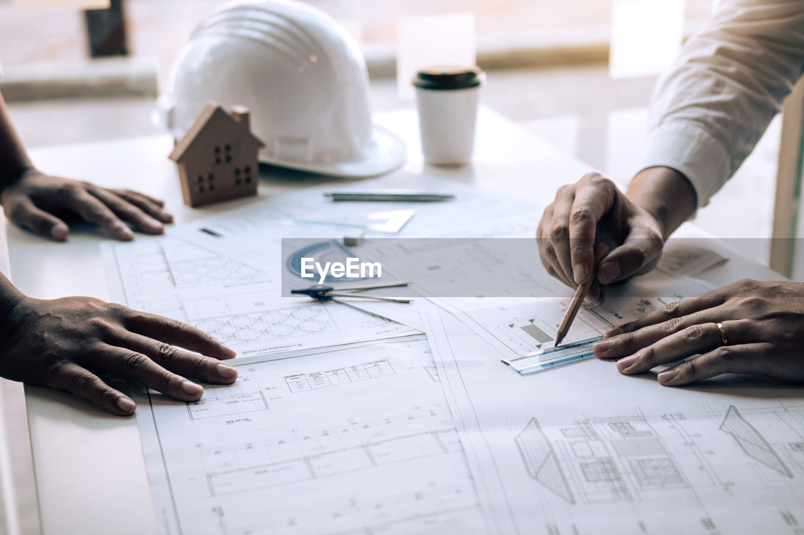 Cropped hands of male architects drawing blueprint at desk