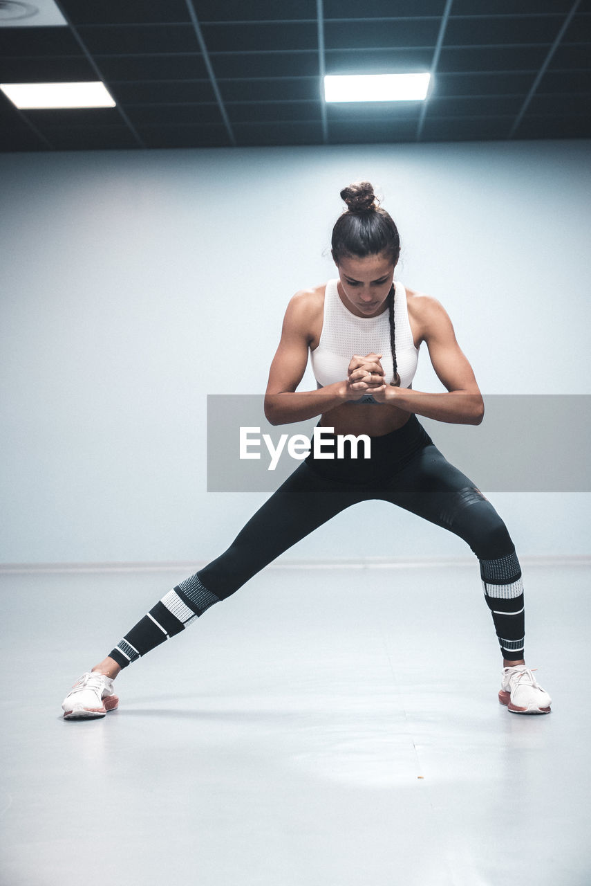 indoors, one person, lifestyles, full length, exercising, front view, young adult, young women, sport, healthy lifestyle, sports clothing, practicing, real people, flexibility, leisure activity, adult, women, clothing, wall - building feature, beautiful woman, body conscious, hairstyle