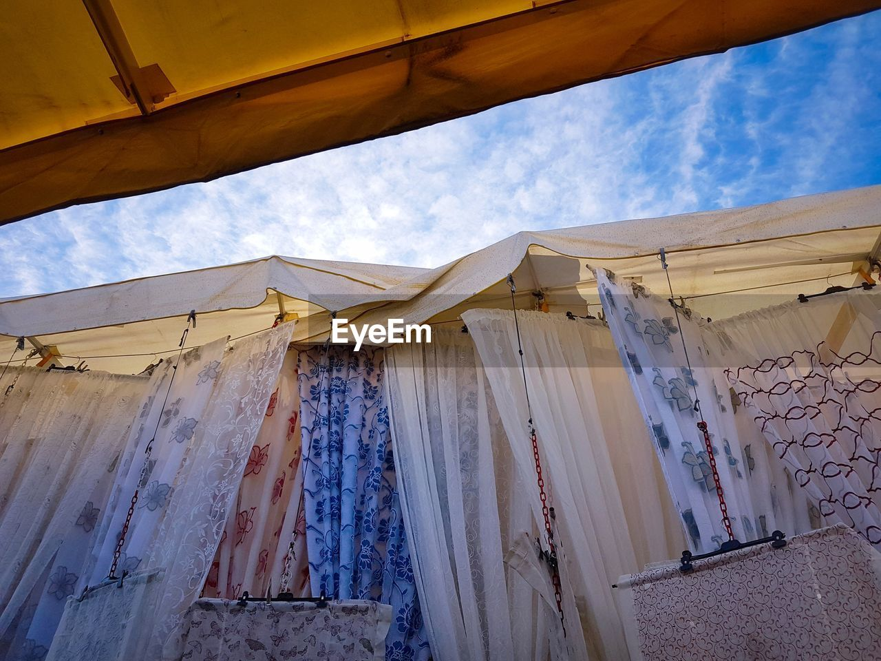architecture, sky, curtain, built structure, low angle view, window, textile, day, cloud - sky, no people, building exterior, drying, outdoors, nature