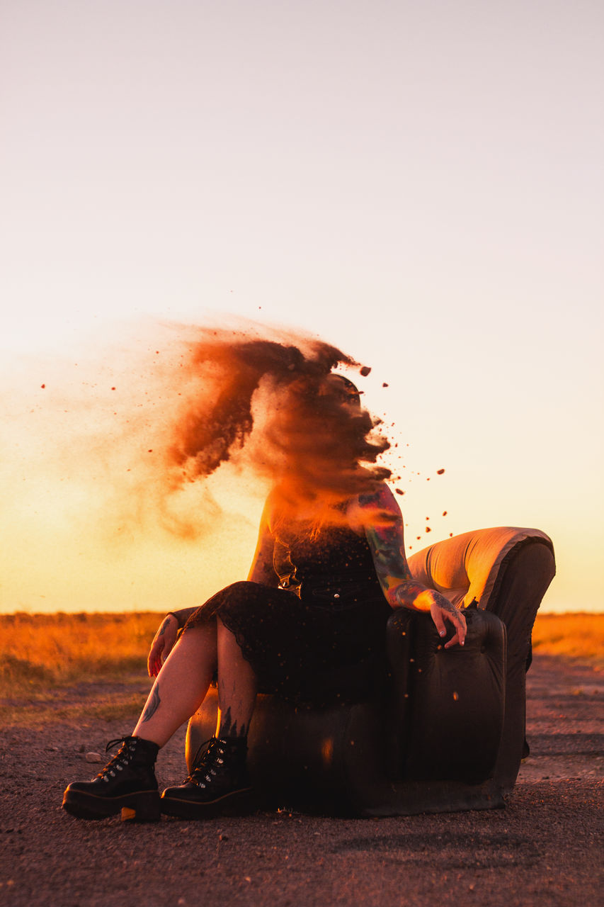 Sand falling on woman sitting against clear sky during sunset