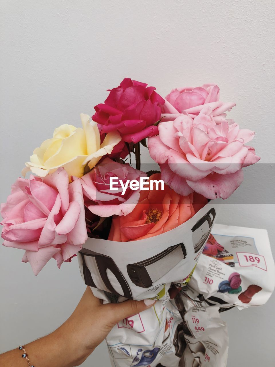 CLOSE-UP OF HAND HOLDING BOUQUET OF ROSE