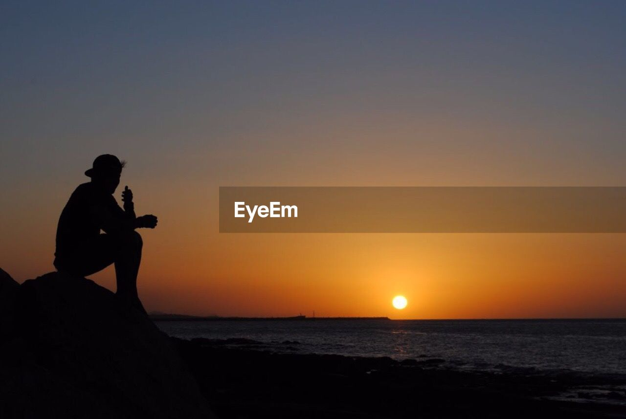 Silhouette Man Sitting At Beach Against Sky During Sunset