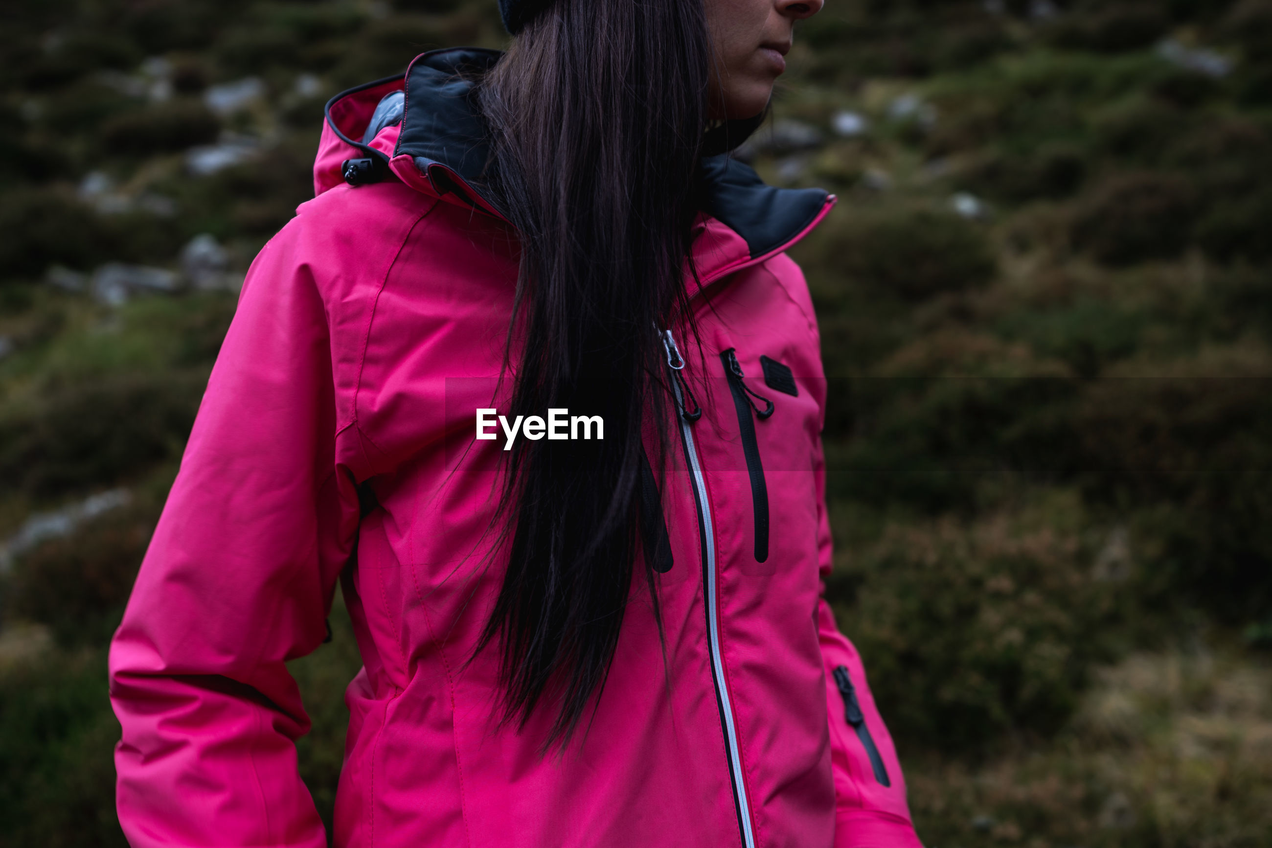 Midsection of woman wearing pink jacket while standing on land