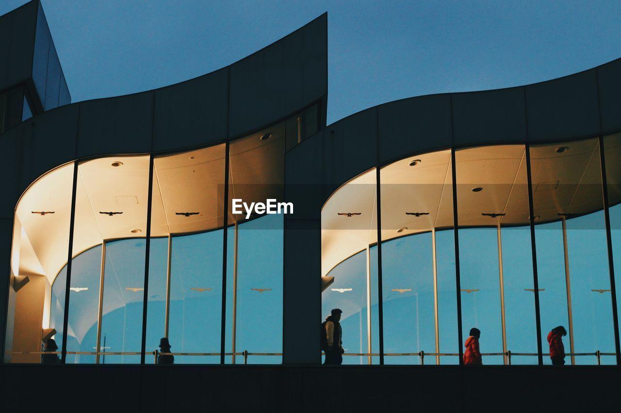 PEOPLE WALKING ON MODERN BUILDING AGAINST BLUE SKY