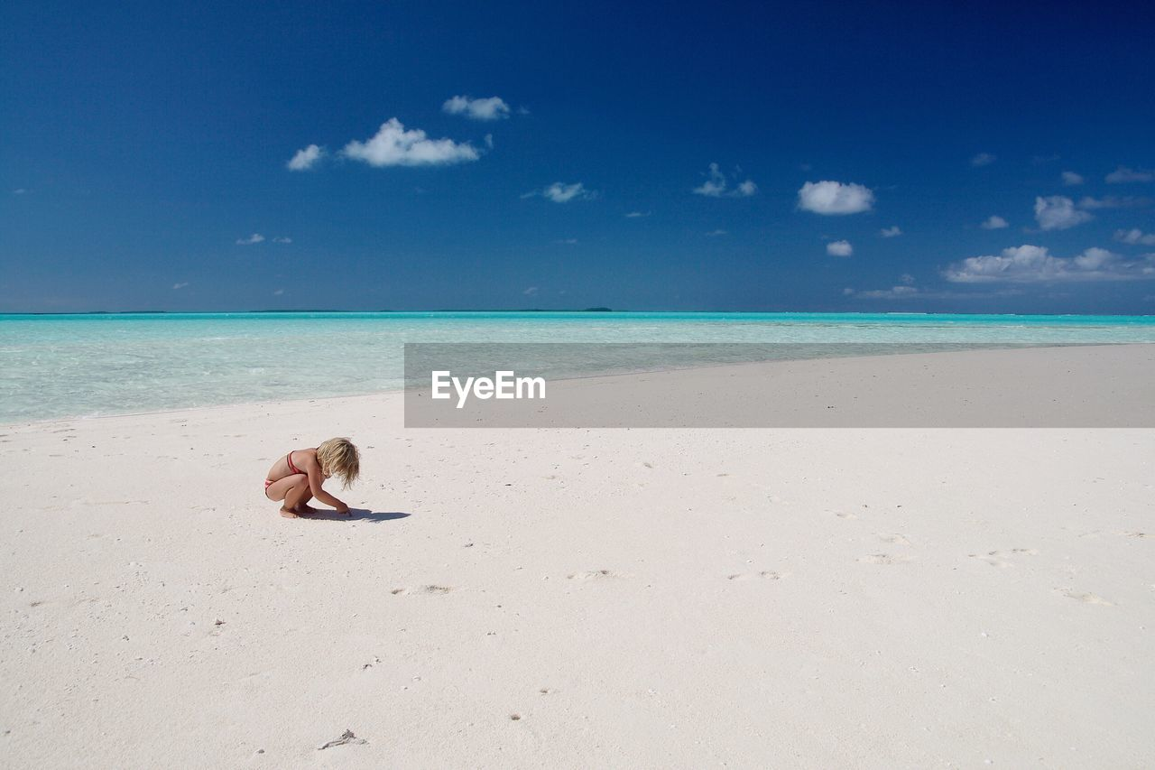 View Of Girl Playing On Beach Against Blue Sky