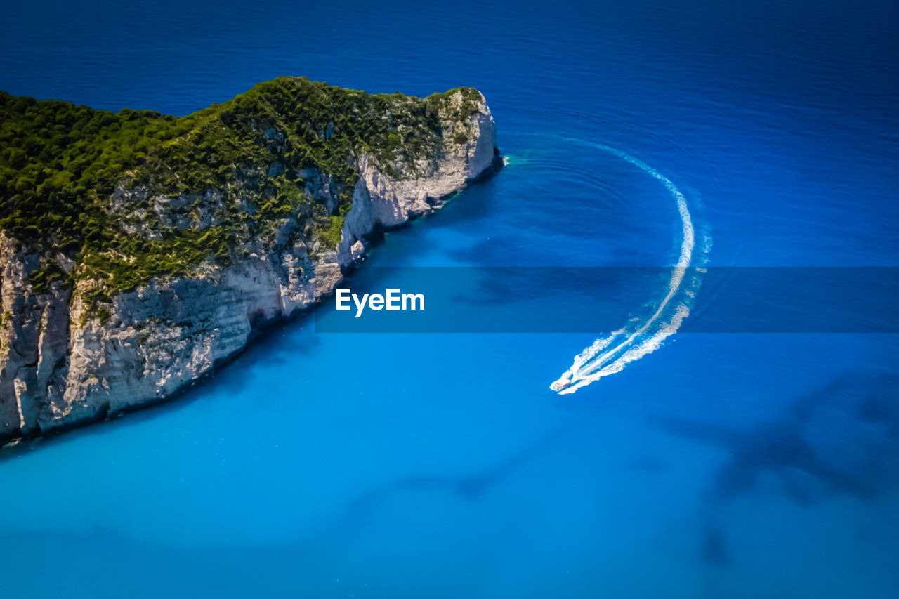High angle view of motorboat sailing by mountain