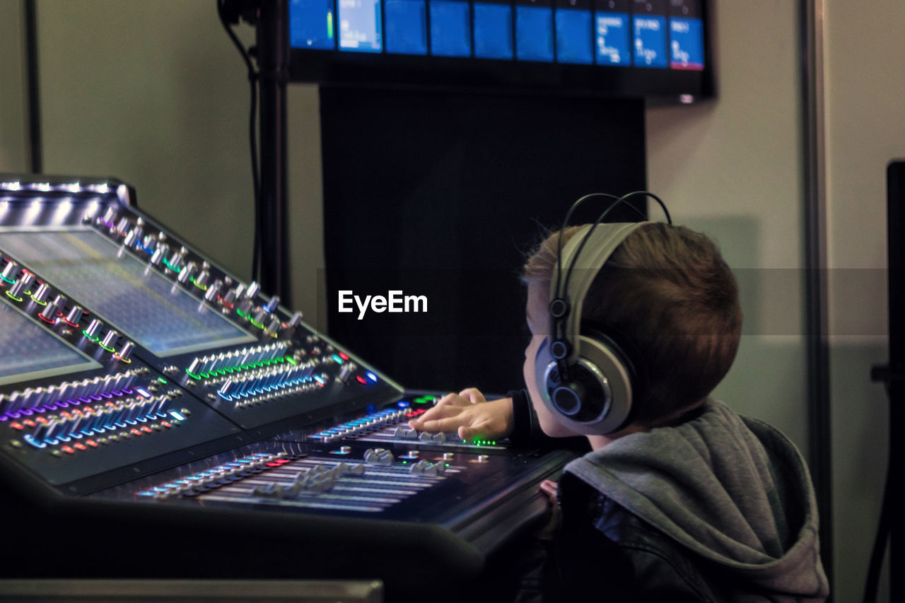 music, technology, real people, arts culture and entertainment, sound mixer, men, indoors, recording studio, sound recording equipment, child, one person, childhood, audio equipment, control, studio, boys, waist up, males, lifestyles, mixing, push button