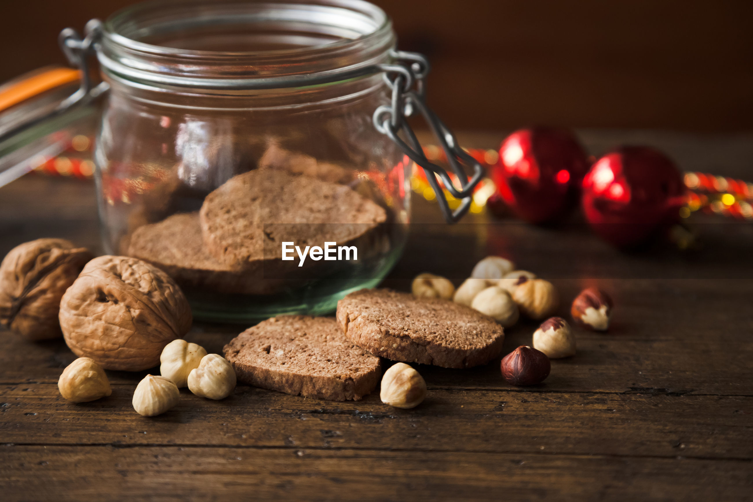 Close-up of cookies and walnuts by jar on table