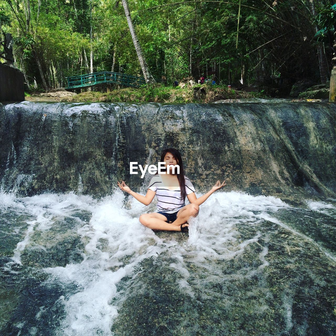 Beautiful Young Woman Sitting In Lotus Position Amidst Waterfall