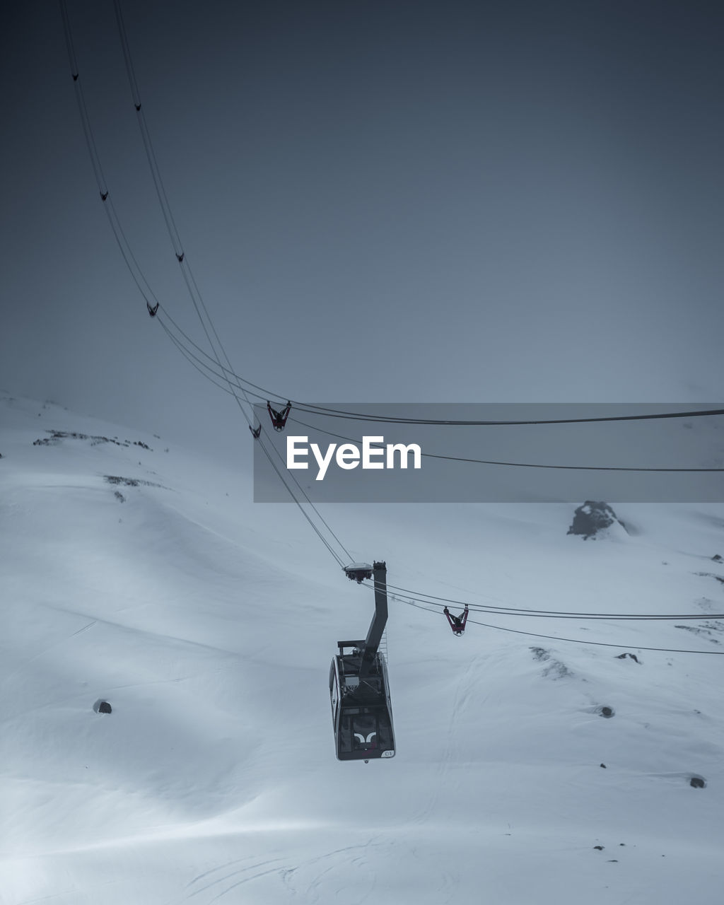 winter, cold temperature, cable, snow, sky, cable car, ski lift, scenics - nature, covering, beauty in nature, overhead cable car, tranquility, mountain, nature, low angle view, tranquil scene, no people, environment, land, snowcapped mountain, electricity