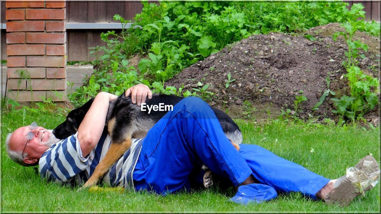 Full Length Of Senior Man Playing With Dog While Lying On Grassy Field