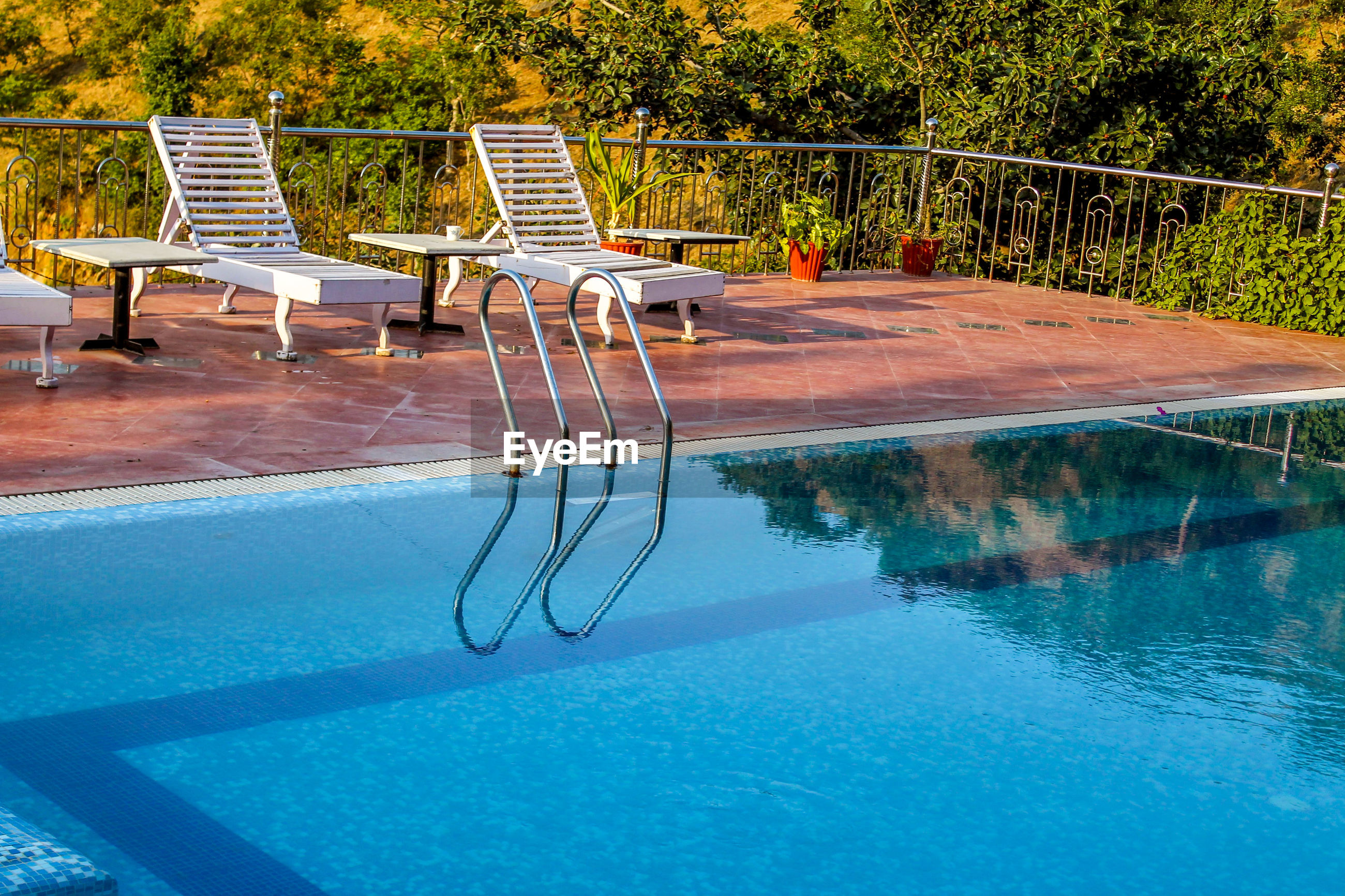 EMPTY CHAIRS ON SWIMMING POOL