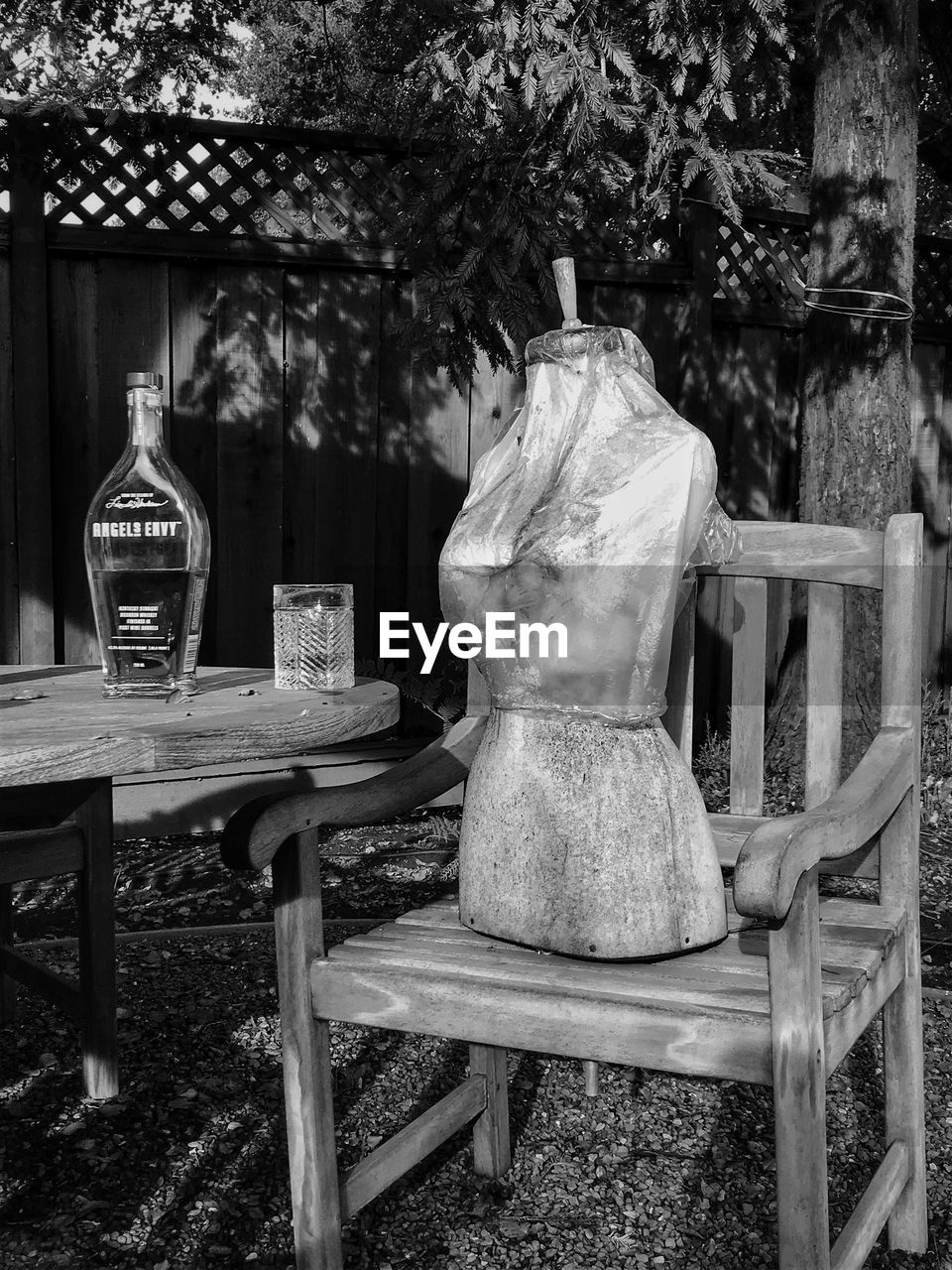 no people, tree, table, chair, seat, plant, day, front or back yard, nature, wood - material, bottle, food and drink, absence, park, still life, outdoors, human representation, container, park - man made space, focus on foreground, glass