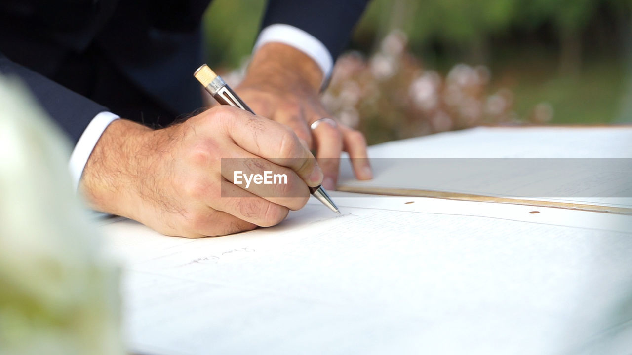 Midsection of bridegroom signing on book at wedding ceremony