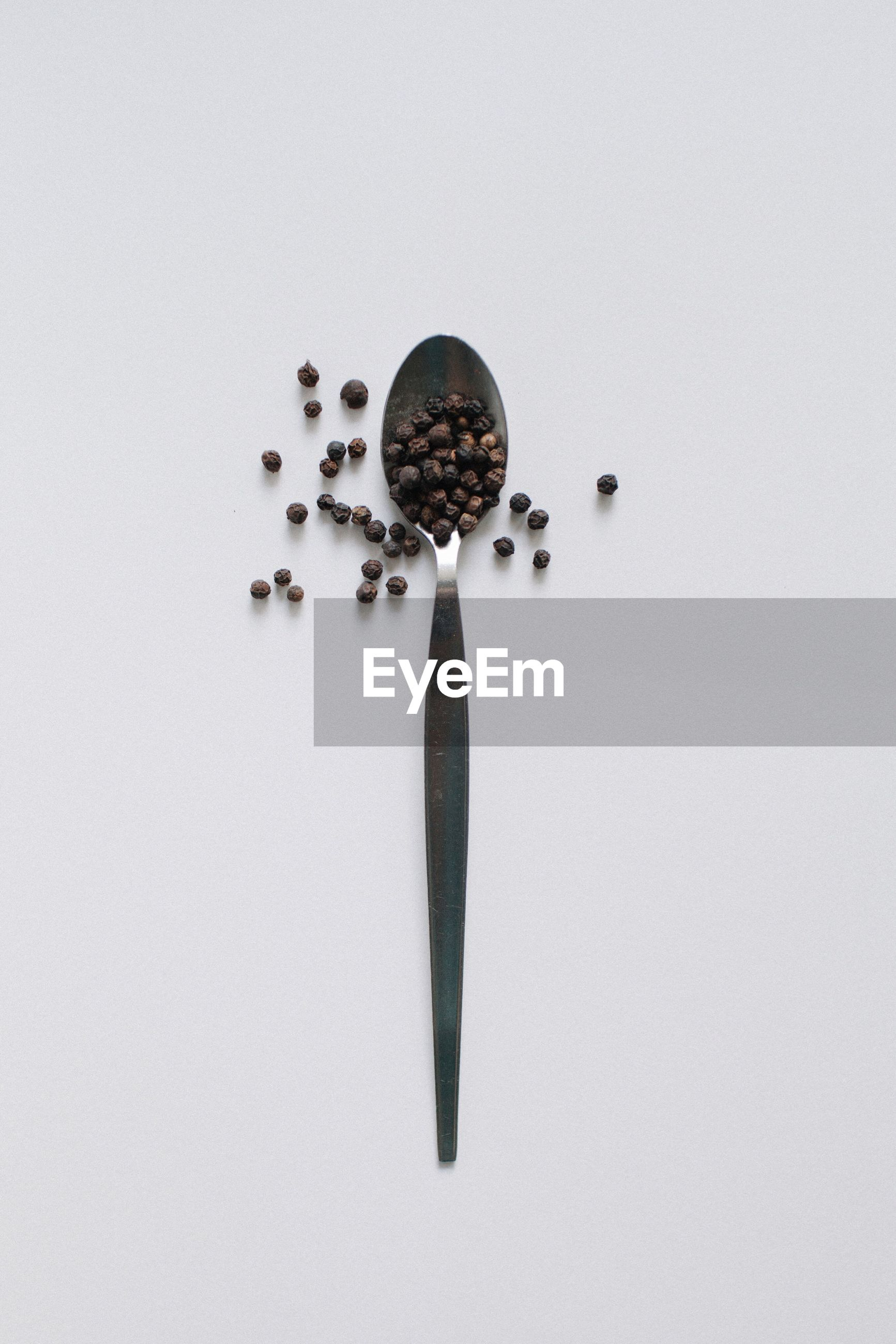 High angle view of black peppercorn in spoon against white background