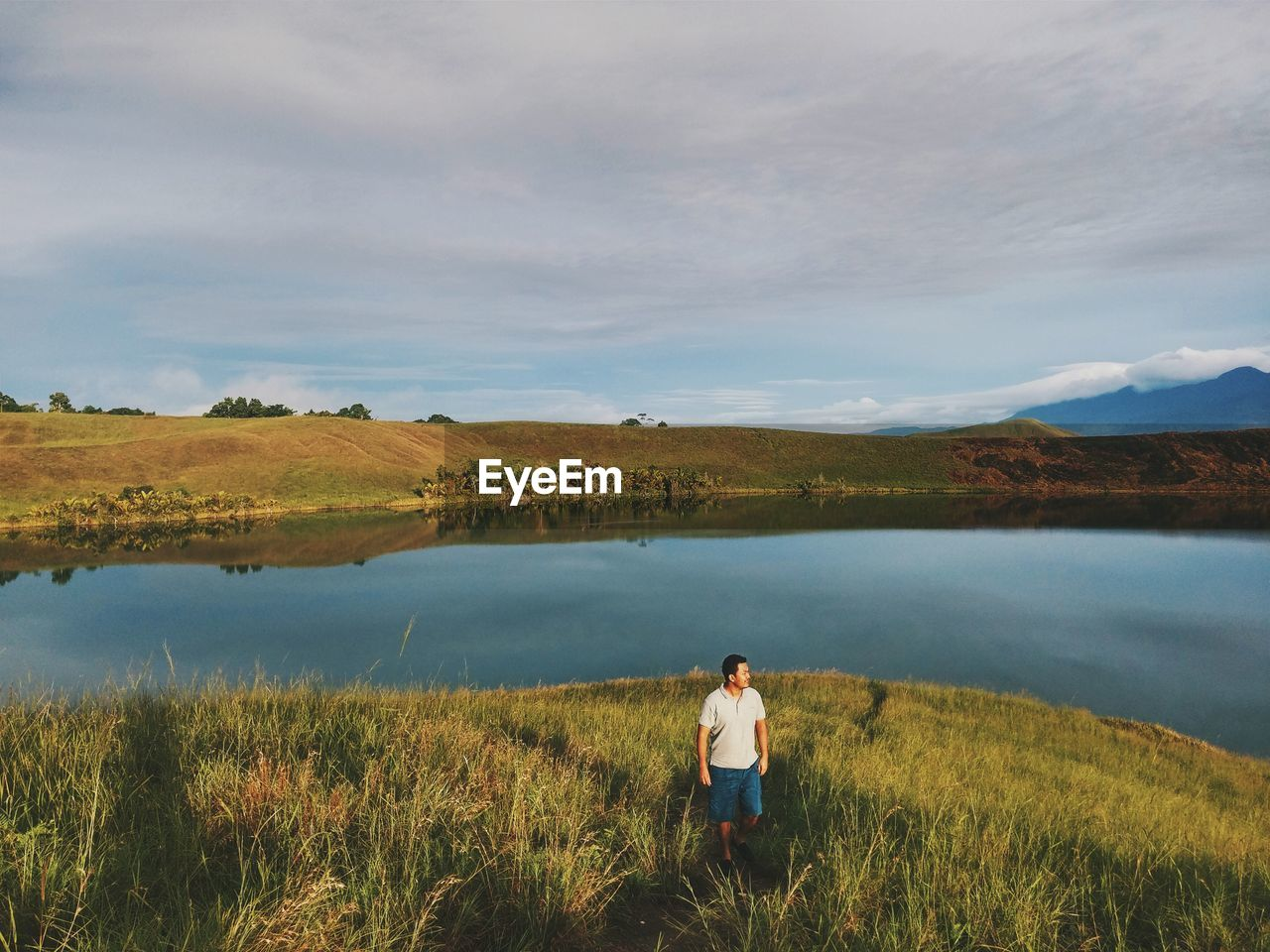 High Angle View Of Man Standing On Grassy Field By Lake Against Cloudy Sky