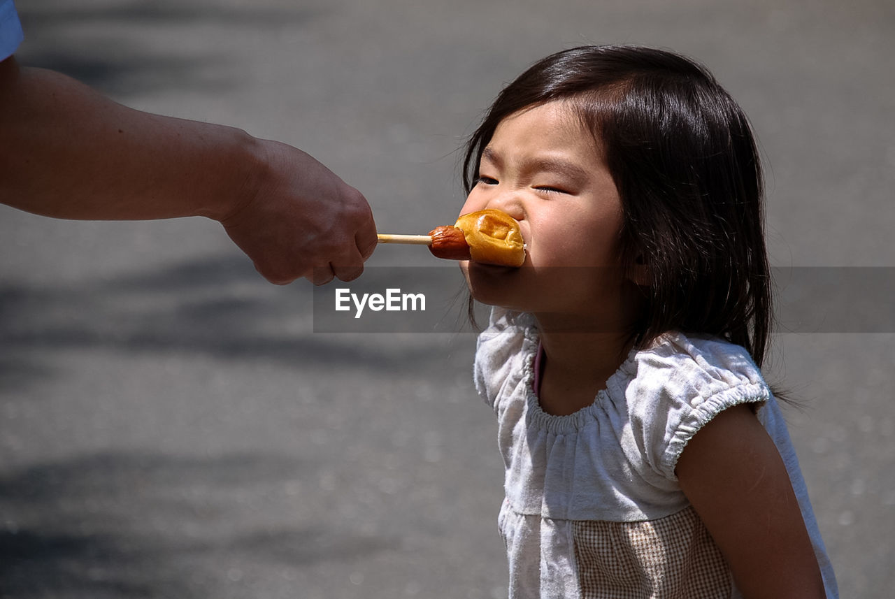 Cropped Hand Of Father Feeding Bread To Daughter On Street