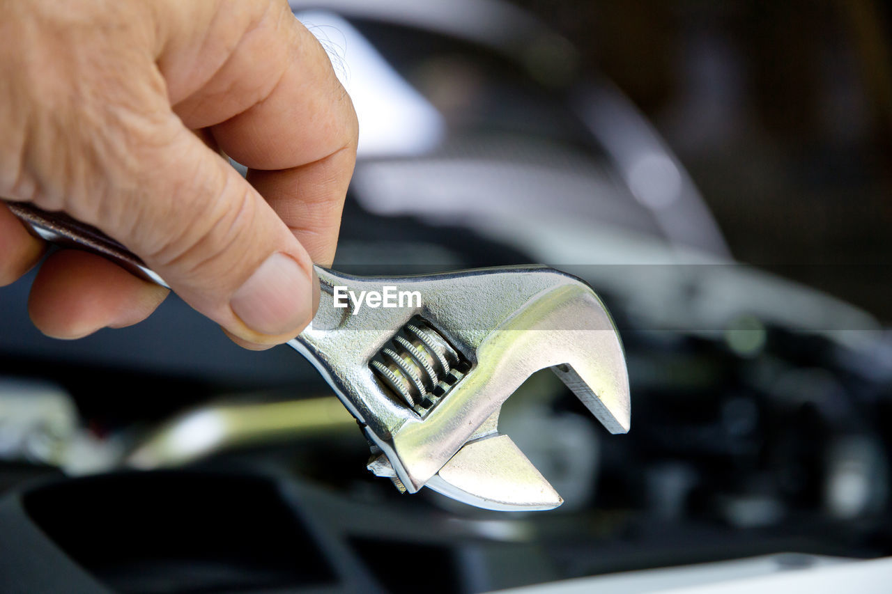 Close-up of man holding wrench against car