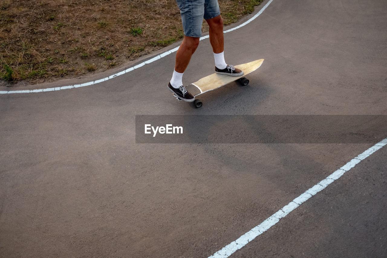 LOW SECTION OF MAN SKATEBOARDING ON SKATEBOARD ON STREET